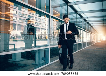 Businessman walking with luggage and using mobile phone at airport. Young man on business trip text messaging from his cell phone.