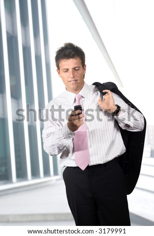Businessman walks in front of a modern office building and he dials on a mobile phone.