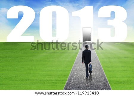 Businessman walks with suitcase on the path lead to the future in 2013