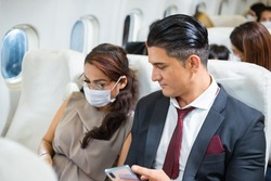 Businessman watching on smartphone with Asian woman sitting at seat in airplane cabin. passengers travel by plane for working trip,