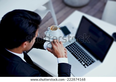 Businessman watching the time in his wear watches,brunette businessman checking the time on his wrist watch, executive looking at the time on his wrist watch, man sitting at table  at business meeting