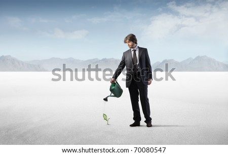 Businessman watering a plant in a desert