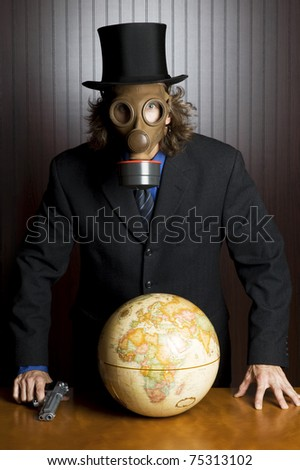 Businessman wearing a gasmask and holding a gun standing over an earth globe on a table