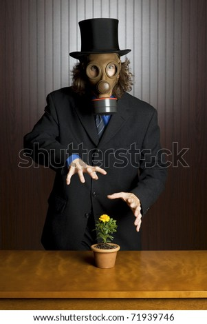 Businessman wearing a gasmask waving his hands over a flower on a table