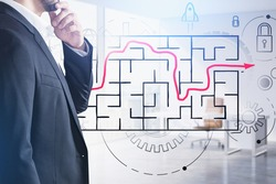 Businessman wearing formal suit is standing and touching his chin with a hand. Sketch with labyrinth with red line, padlock, cogwheel, rocket start up. Office in background. Concept of making decision