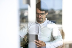 Businessman wearing glasses sitting looking to his tablet. Successful male portrait with positive attitude working from home