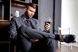 Businessman wearing in suit. Businessman drinking red wine and thinking about business.