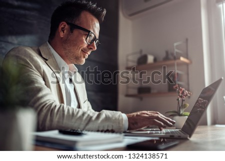 Businessman wearing linen suit and eyeglasses sitting at his desk by the window and using laptop in the office