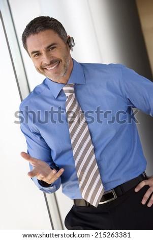 Businessman wearing mobile phone hands-free device, making hand sign, smiling, portrait (tilt)