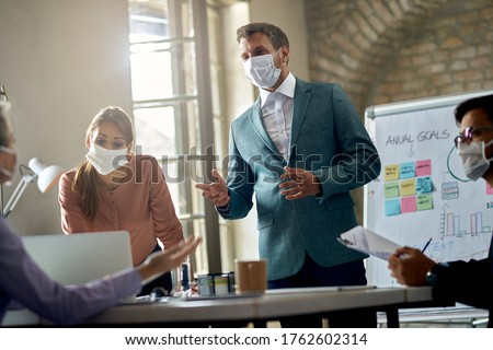 Businessman wearing protective face mask while holding a presentation on a meeting during coronavirus epidemic.