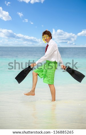 Businessman wearing snoring mask with flippers and wearing formal clothes with red tie entering water on the beach - stock photo