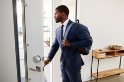 Businessman Wearing Suit Opening Door Leaving Home For Work