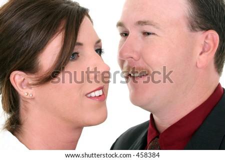 Businessman Whispering In Woman's Ear.  Focus on Woman.