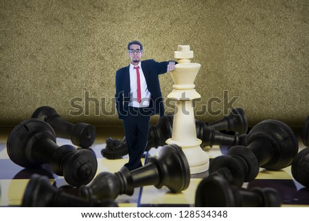 Businessman winning chess game on brown background