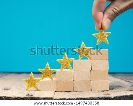 Businessman with a big golden star, rating or ranking system concept with wooden stairs #1497430358