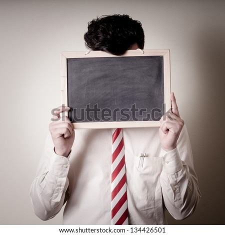 businessman with a blank blackboard on face on gray background - stock photo