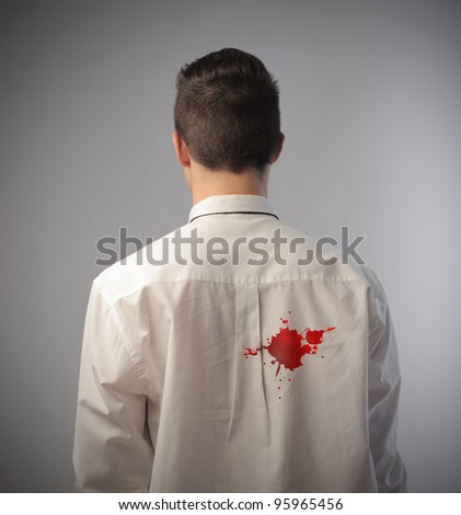Businessman with a blood stain on the back of his shirt