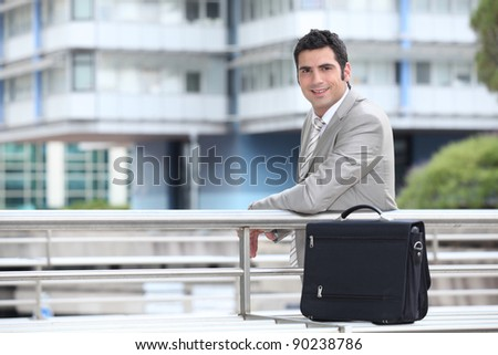 Businessman with a briefcase standing in an urban environment