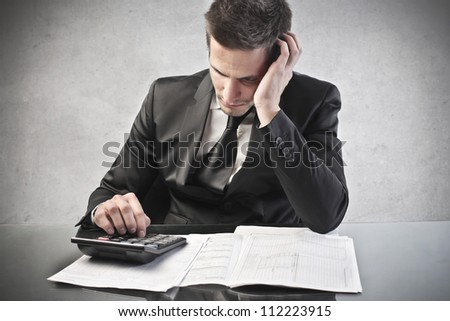 Businessman with a calculator. Concentration