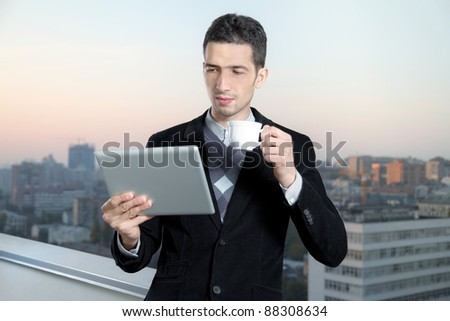 Businessman with a cup of coffee uses a digital tablet on the roof of business center. Cityscape on background.