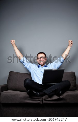 businessman with a laptop raises his arms while sitting on the couch