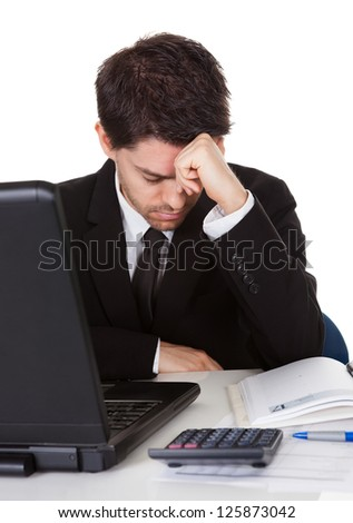 Businessman with a look of hopelessness staring at the screen of his laptop with his head resting in his hands