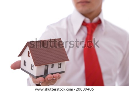 businessman with a mini house for real estate concept presentation