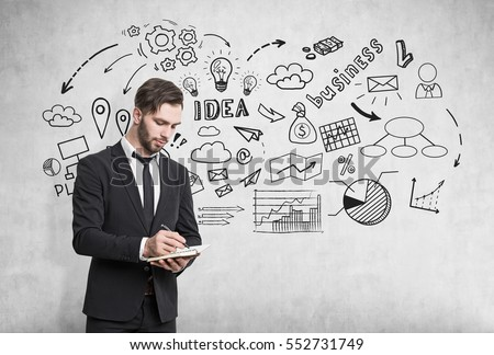 Businessman with a notebook is writing while standing near a concrete wall with a business idea sketch drawn on it.