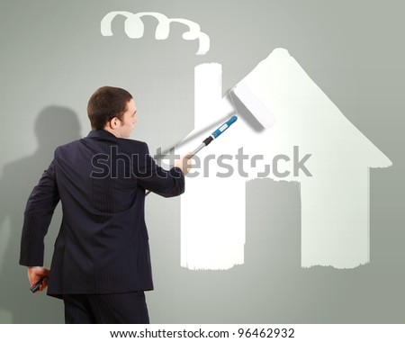 Businessman with a paint brush and picture of house on the wall