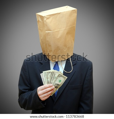 Businessman with a paper bag on head and dollars notes in arm - stock photo