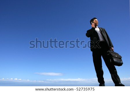 Businessman with a suitcase and a phone - stock photo
