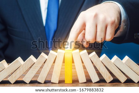 Businessman with a touch stops process of falling dominoes. Successful strong business, solve all accumulated problems. Stop destructive processes. Risk management concept. Debt restructuring Foto d'archivio ©