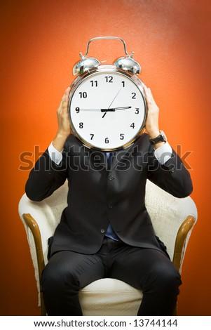 Businessman with alarm clock on head, studio shot. - stock photo