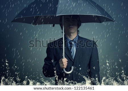 Businessman with an umbrella in the rain.
