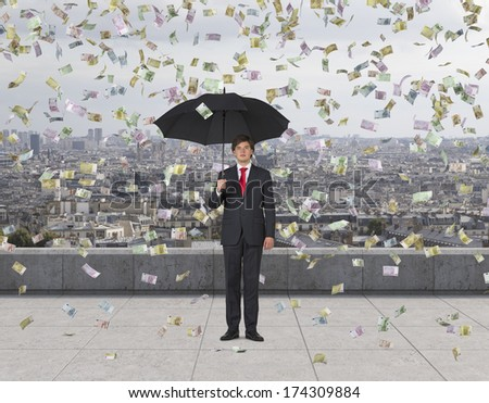 Businessman with an umbrella under the euro rain, roof terrace 2