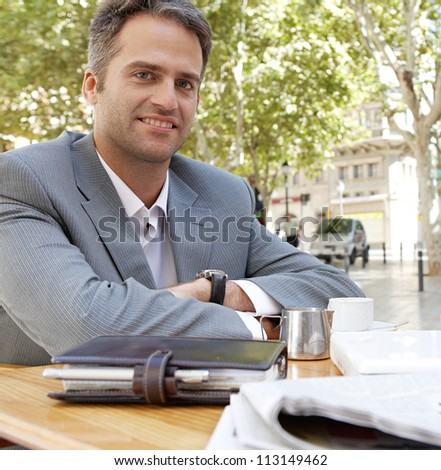 Businessman with arms crossed sitting at a coffee shop table outdoors, smiling.
