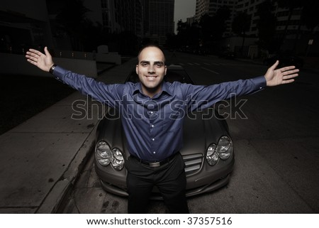 Businessman with arms extended and a luxury car in the background