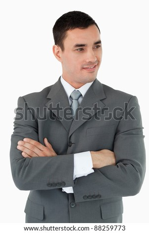 Businessman with arms folded looking to the side against a white background