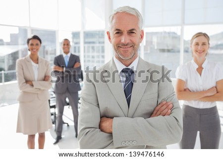 Businessman with arms folded standing in front of colleagues behind him