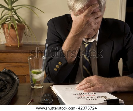 Businessman with bad sales report, drinking alone, showing frustration and anxiety