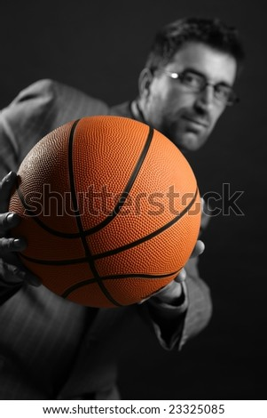 Businessman with basketball ball, teamwork, leadership metaphor - stock photo