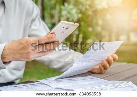 Businessman with bills and smart phone at the table. Calculation of costs
