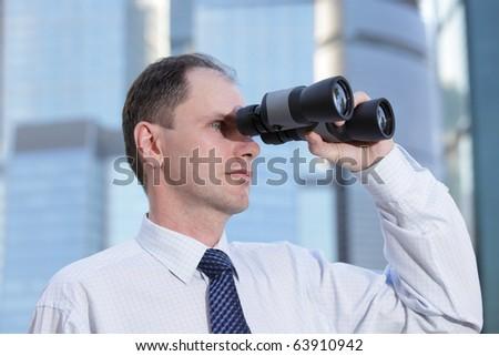 Businessman with binoculars against modern office buildings