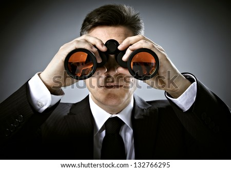 Businessman with binoculars. Over gray background.