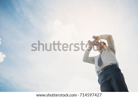 Businessman with binoculars spying on blue sky. Businessman Hand Holding / looking / watching using Binoculars.