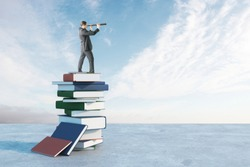 Businessman with binoculars standing on book pile. Blue sky background. Future and vision concept
