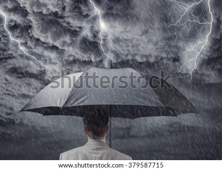 Businessman with black business umbrella protecting himself from the storm concept for insurance, financial protection from recession or economic depression
