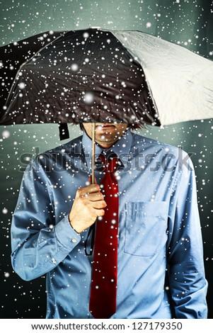 Businessman with black umbrella in snow storm. Financial problems, economic crisis, business challenge concept.