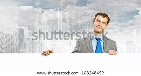 Businessman with blank banner standing against urban scenic. Place for text