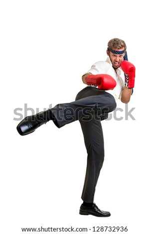 Businessman with boxing gloves kicking high